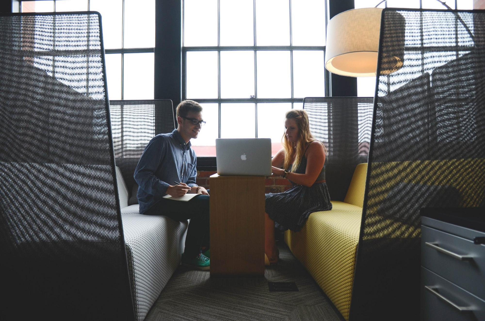 Kaksi henkilöä istuu vierekkäin. Katsovat tietokonetta.